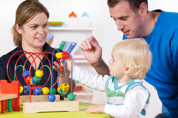 a speech therapist working with a child and parent
